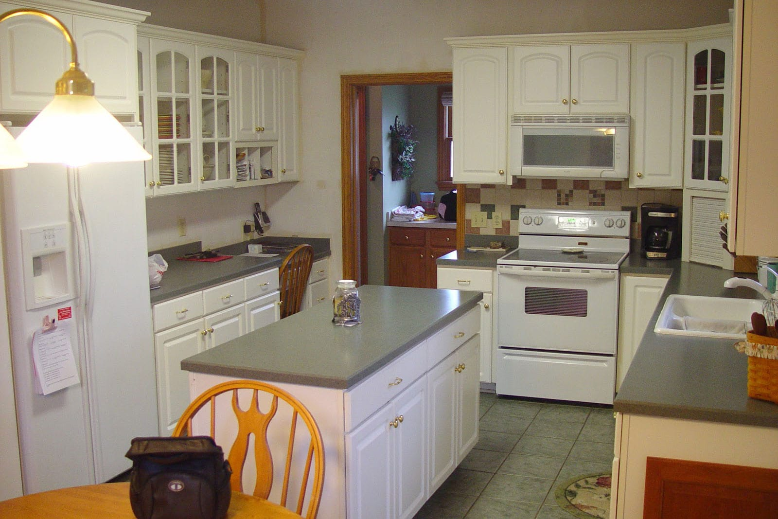 old painted white kitchen before kitchen refacing with center island and the cabinet does not extend to the ceiling