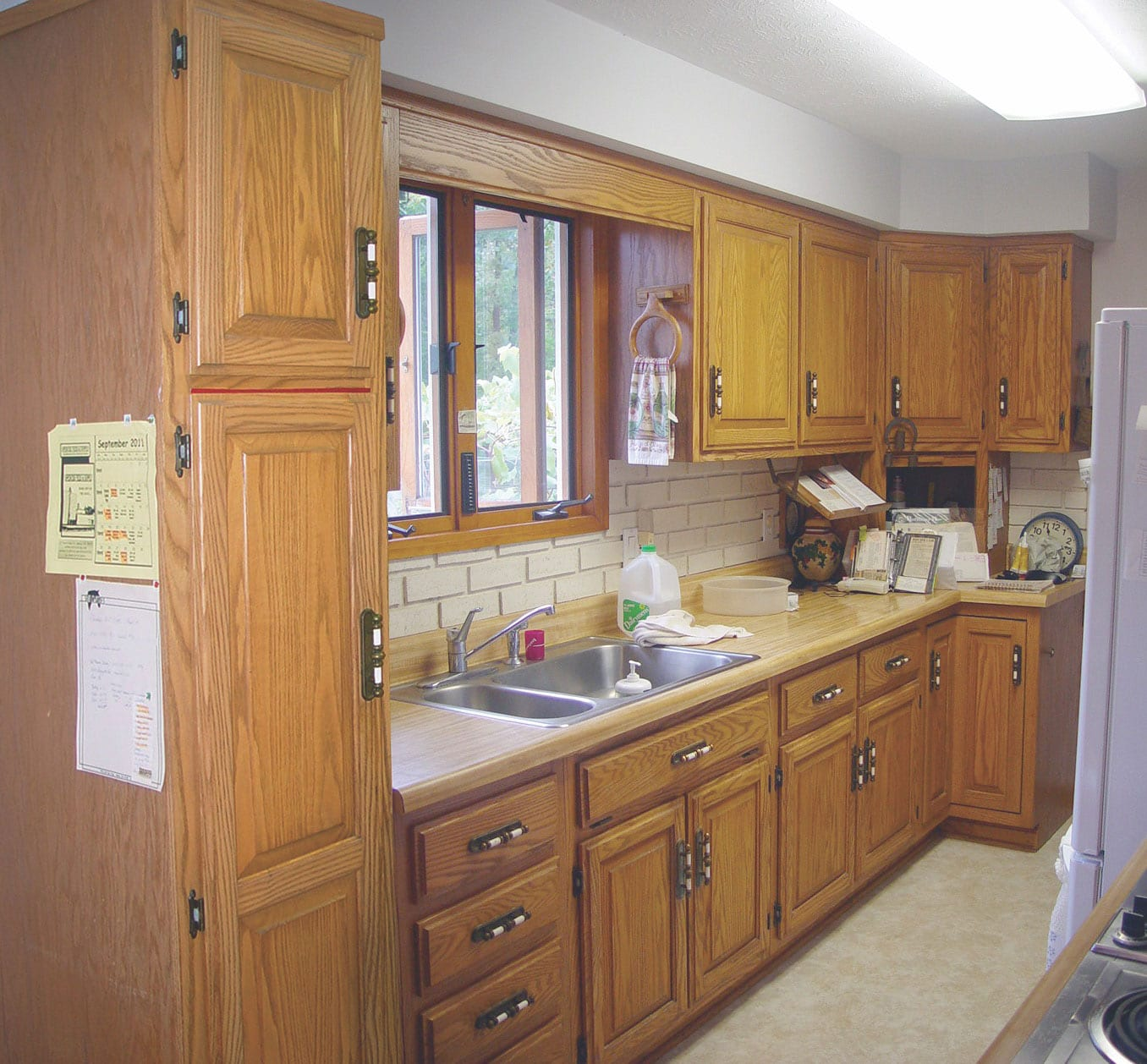 a picture of an old kitchen and brown cabinets made from wood and the cabinets not extend to the ceiling