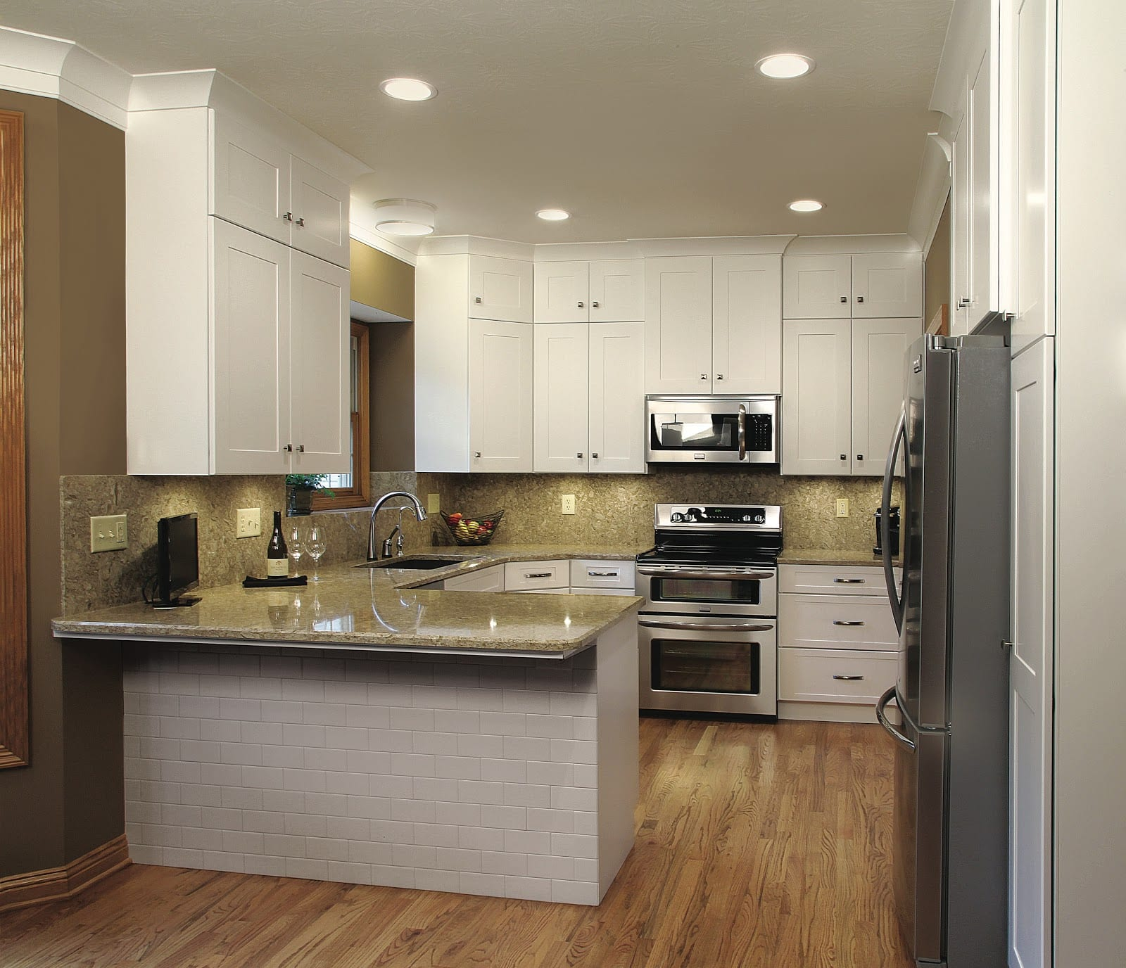 a picture of the kitchen after refacing featuring a white cabinet extended to the ceiling and will cornered countertop and proper placement of the appliances
