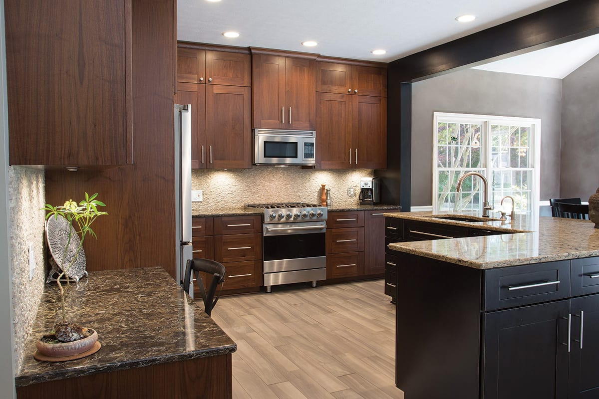 a picture of a brown kitchen after a refacing cabinet project in Ohio, featuring the proper position of appliances and a centre island with a sink