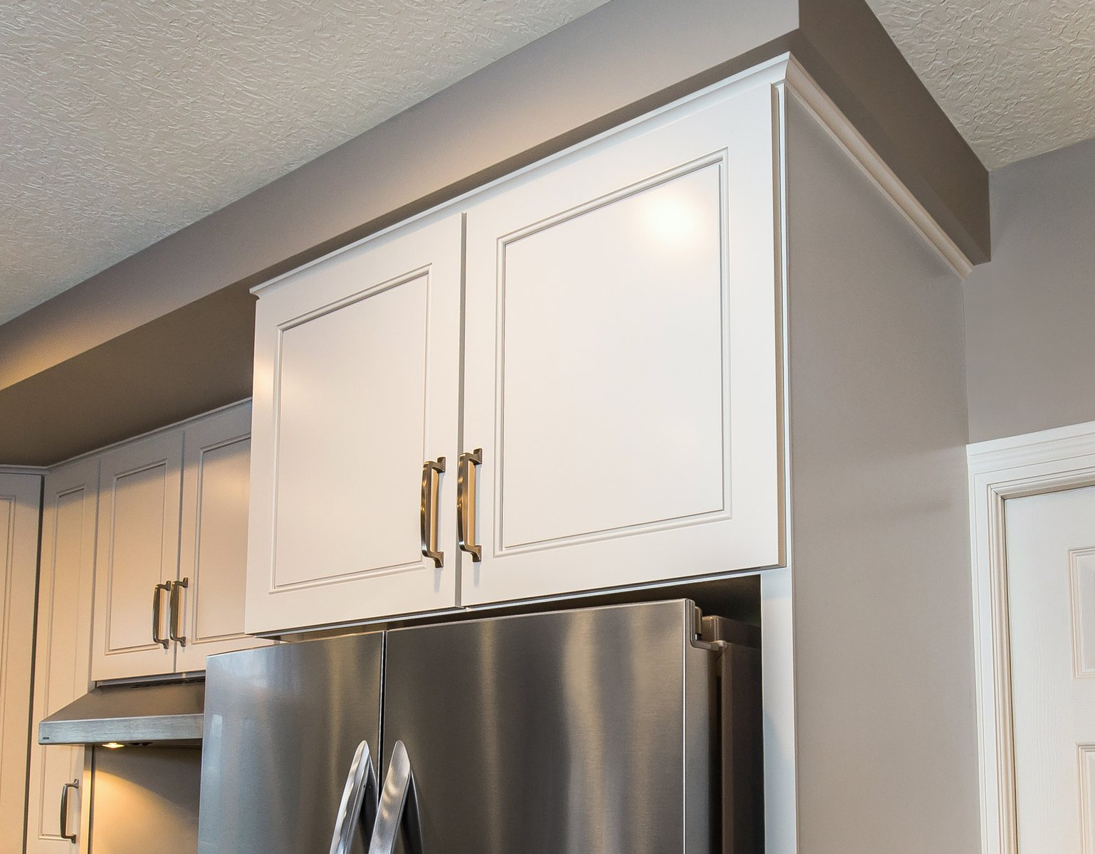 White refaced kitchen cabinets above a silver refrigerator
