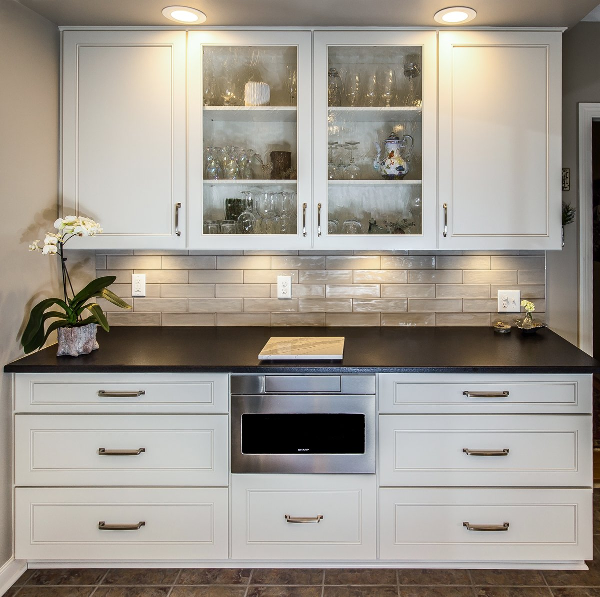 A set of white kitchen cabinets with a black countertop